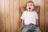 Young boy sitting in a chair with mouth open wide