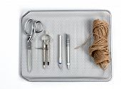 High angle shot of twine, a compass, knife, pen and scissors in a mesh in-box tray on a white office
