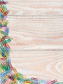 Paper clips rn random pattern on two sides of the image. A whitewashed wood background with multi co