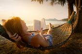pic of rest-in-peace  - Young lady reading a book in hammock on a beach at sunset - JPG