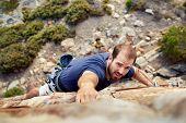 picture of cliffs  - A man reaching for a grip while he rock climbs on a steep cliff - JPG