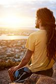 stock photo of dreadlocks  - A man in dreadlocks on a mountain looking at the view - JPG