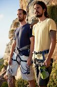 Two men looking at the view from the mountain with their rock climbing equipment on