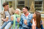 friendship, travel, drink and vacation concept - group of smiling friends with take away coffee