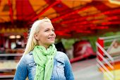 leisure, amusement park and people concept - smiling young woman in amusement park with carousel on