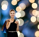 shopping, sale, banking, money and holidays concept - smiling woman in dress with shopping bags and