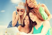summer holidays, vacation, internet and technology concept - smiling girls looking at tablet pc in c