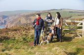 Family With Dog Walking Along Coastal Path