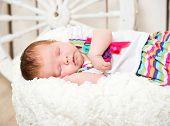 cute newborn baby sleeping on the colorful dress