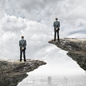 Rear view of business people standing on edge of rock