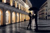 Couple standing in the raining street in the night.