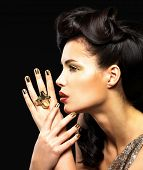 Beautiful  woman with golden nails and fashion makeup of eyes. Brunet girl model with style hairstyle on black background