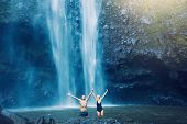 Couple enjoying pool at the base of large waterfall in Hawaii