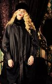 Gorgeous fashion model with magnificent blonde hair in a rich historical costume. Fur clothing. Vintage. Luxury style.