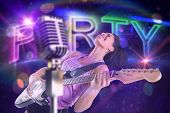 Pretty girl playing guitar against digitally generated colourful party text
