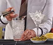 Bartender preparing cocktail drinks pouring liquor on iced glass.Barman preparing cocktail drinks.
