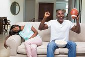 Bored woman sitting next to her boyfriend watching football at home in the living room