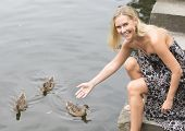 stock photo of canard  - blond woman sitting by the water with ducks - JPG