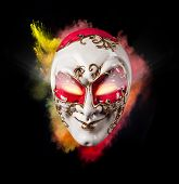 Isolated Venice mask with freeze motion of colored powder on black background