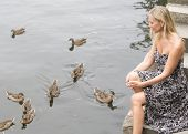 pic of canard  - blond woman sitting by the water with ducks