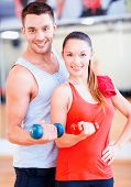 fitness, sport, training, gym and lifestyle concept - two smiling people working out with dumbbells in the gym