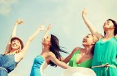 summer holidays and vacation concept - smiling girls with hands up on the beach