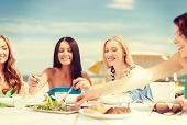 summer holidays and vacation concept - smiling girls in cafe on the beach