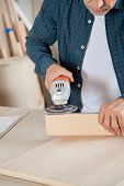 Midsection of senior carpenter using electric sander on wood in workshop