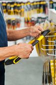 Midsection of senior salesman holding hacksaw in hardware store