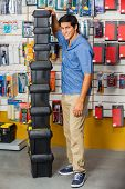 Full length portrait of smiling young man with stacked toolboxes in hardware store