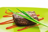 meat savory : grilled beef fillet mignon served on green plate isolated over white background with c