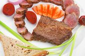 main course : roast red meat slices served on white plate with tomatoes , sprouts and bread  isolated on white background