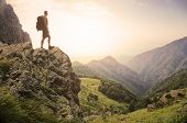 image of mountain-climber  - Healthy young man standing on top of a high in the mountains enjoying the natural beauty in the morning light - JPG