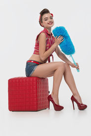 picture of halter-top  - Glamorous young smiling maid wearing great red halter top blue shorts with the duster sitting on the padded stool satisfied with her life - JPG