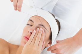 stock photo of eyebrows  - Close up of a hands threading beautiful woman - JPG