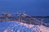 Ski lifts in early morning lit.