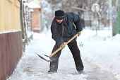 stock photo of shovel  - Caucasian woman cleaning snow from sidewalk with shovel - JPG