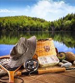 foto of fly rod  - Fly fishing equipment on deck with beautiful view of a lake - JPG