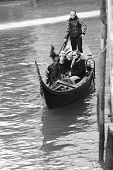Gondolier Carrying Tourists In Venice, Black And White