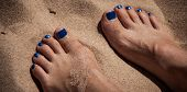 stock photo of toe nail  - Painted toe nails at a beach in summer - JPG
