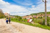 two female hikers walking on village road near Biertan in Transylvania Romania
