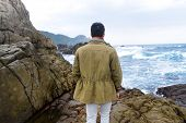 Young man standing on a rock on a rocky beach watching the ocean