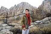 young man in scarf with coat  on a rock at beach