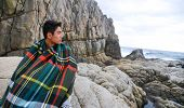 young man warmed up in plaid pattern scarf sitting on a rock at the sea