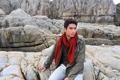 Young man standing on a rocky beach watching the ocean