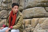 young man in scarf with coat sitting on a rock at beach background