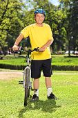 Full length portrait of a mature man in sportswear posing next to his bike in a park