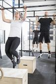 stock photo of pull up  - A group training pull ups or hang ups at a fitness gym center - JPG
