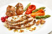 Tasty sliced roasted loin pork with potatoes, bell peppers, gooseberries and asparagus