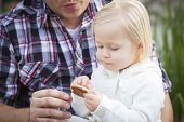Adorable Little Girl Eating a Cookie with Daddy Outside.